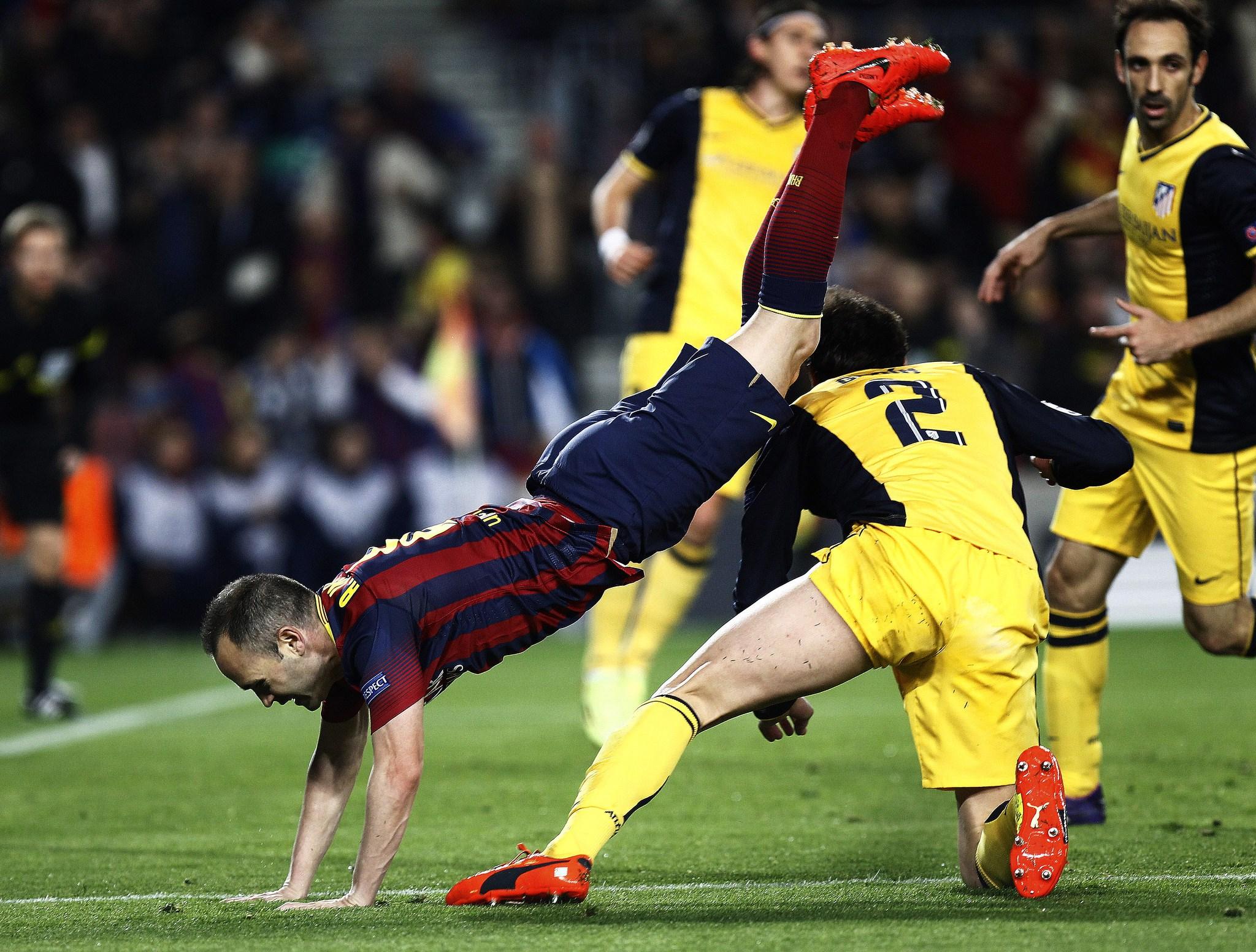 Iniesta é derrubado por Godín durante partida entre Barcelona e Atlético de Madri
