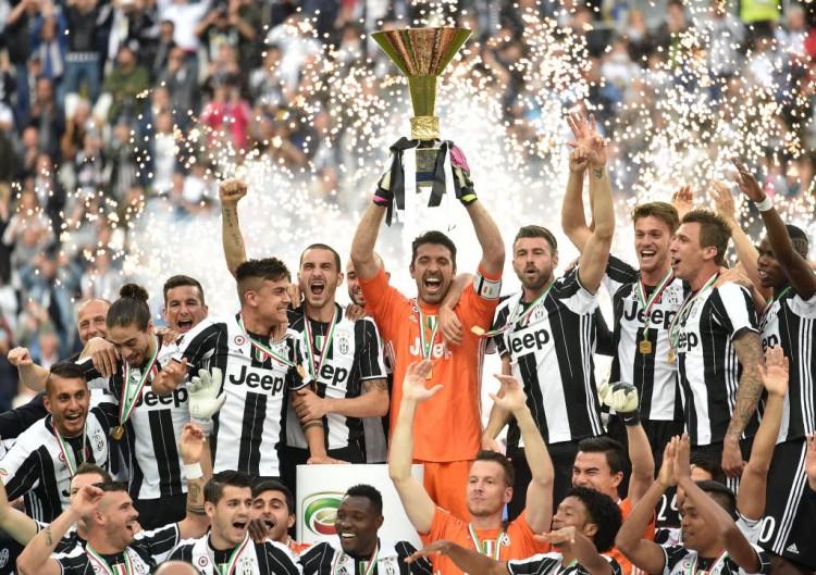 Ladeado por companheiros da Juventus, o goleiro Buffon ergue a taça da Série A (Alberto Lingria - 14.mai.2016/Xinhua)