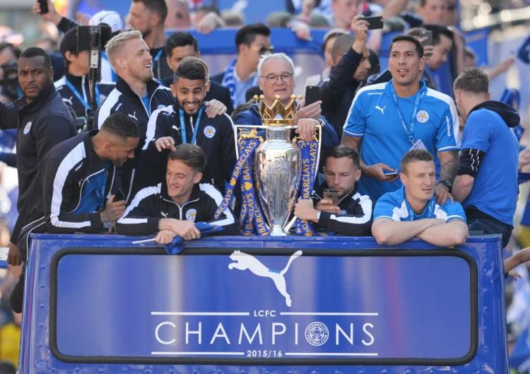 Jogadores do Leicester e o técnioc Ranieri (centro) desfilam e carro aberto pela cidade com a taça da Premier League (Glyn Kirk - 16.mai.2016/AFP)