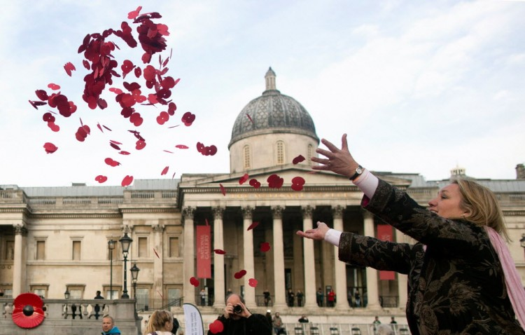 Mulher joga papoulas na Trafalgar Square (praça Trafalgar), em Londres, do Dia do Armistício, dois anos atrás (Andrew Cowie - 11.nov.2014/AFP)