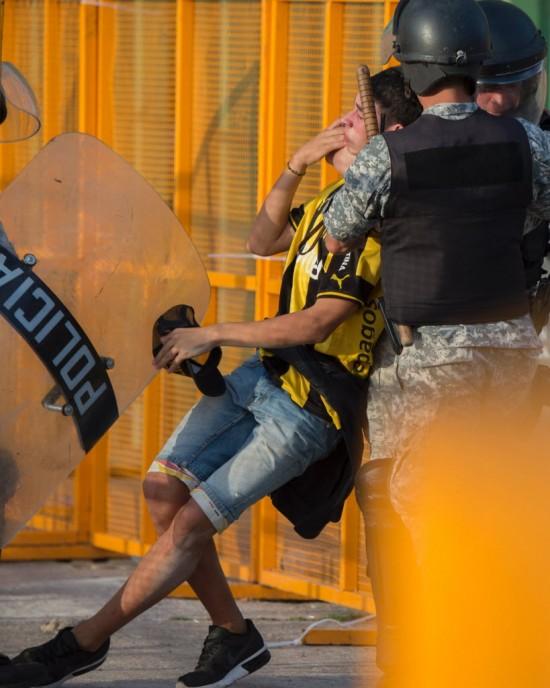 Em Montevidéu, policial prende torcedor do Peñarol antes do clássico com o Nacional, que acabou cancelado (Pablo Porciuncula - 28.nov.2016/AFP)
