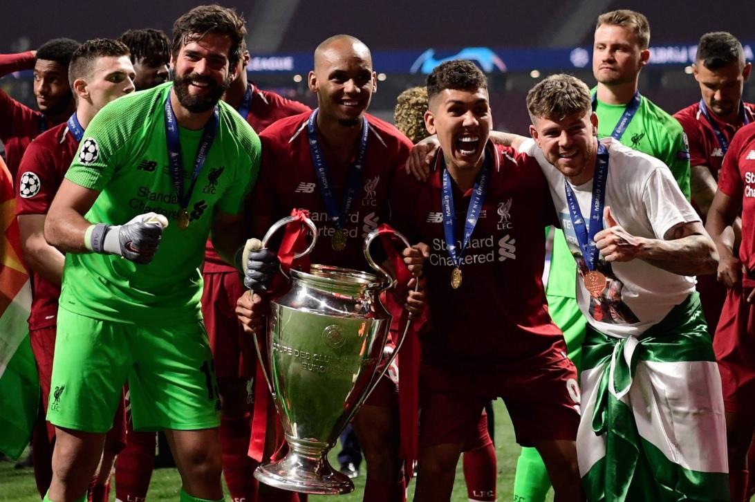 Ladeado pelo goleiro Alisson e pelo atacante Roberto Firmino, Fabinho segura o troféu da Champions League depois da vitória por 2 a 0 sobre o Totenham, em Madri (Javier Soriano - 1º.jun.2019/AFP)